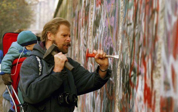 Un hombre con su bebé en la espalda usa un martillo y un cincel para tallar un pedazo del Muro de Berlín  - Sputnik Mundo