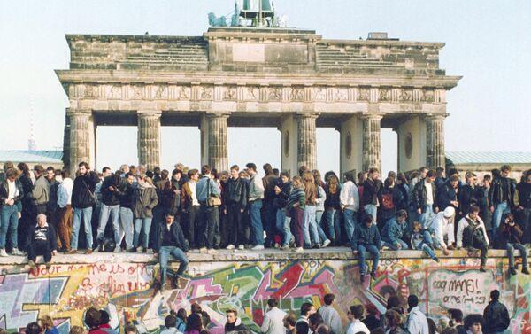 Alemanes de ambos lados se paran en el Muro de Berlín frente a la Puerta de Brandenburgo  - Sputnik Mundo