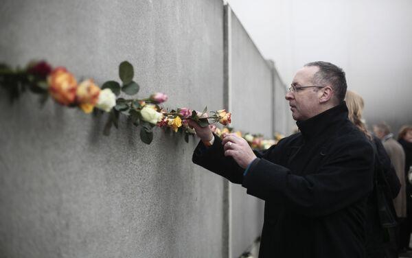 Un hombre coloca una flor en una grieta del antiguo Muro de Berlín para conmemorar a las víctimas del muro en 2014 - Sputnik Mundo