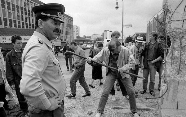 Policía fronterizo de Alemania Oriental observa a un hombre martillando una sección del Muro de Berlín en 1989 - Sputnik Mundo