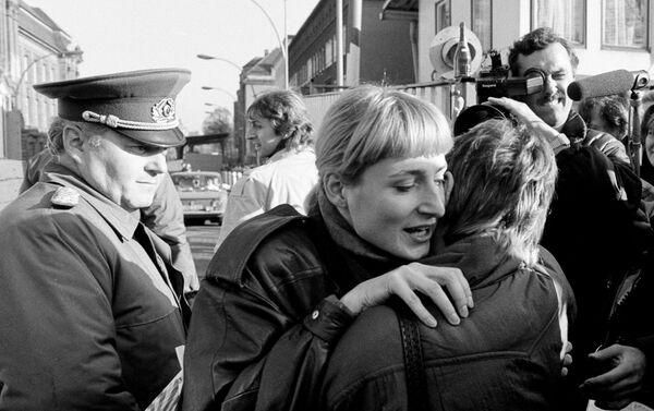 Ciudadanos de Berlín oriental y occidental se abrazan tras la caída del muro mientras un soldado fronterizo los observa - Sputnik Mundo