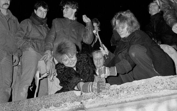 Berlineses rompen con martillo y cincel una sección del Muro de Berlín después de que se anunciara la apertura de la frontera de Alemania Oriental  - Sputnik Mundo