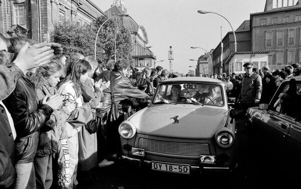 Ciudadanos de Berlín Occidental dan la bienvenida a los alemanes orientales que pasaron el punto de control de la frontera del Muro de Berlín  - Sputnik Mundo