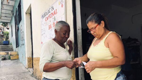 Manuela, dueña de la casa donde está la farmacia comunal, entregando unos medicamentos a una vecina del barrio - Sputnik Mundo