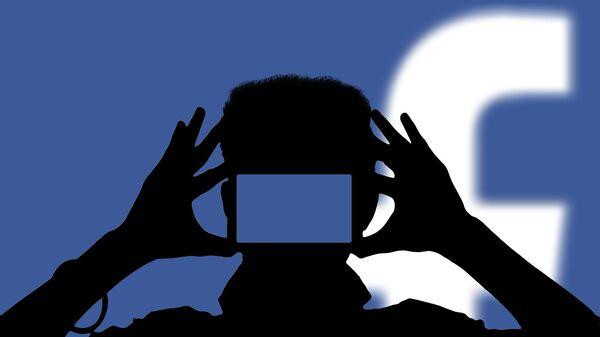 Una persona con un teléfono móvil con el logo de Facebook de fondo - Sputnik Mundo