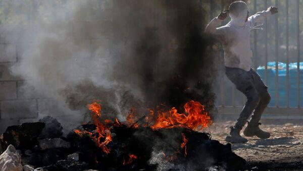 Un manifestante lanza la piedra durante protestas contra la demolición de los edificios palestinos - Sputnik Mundo