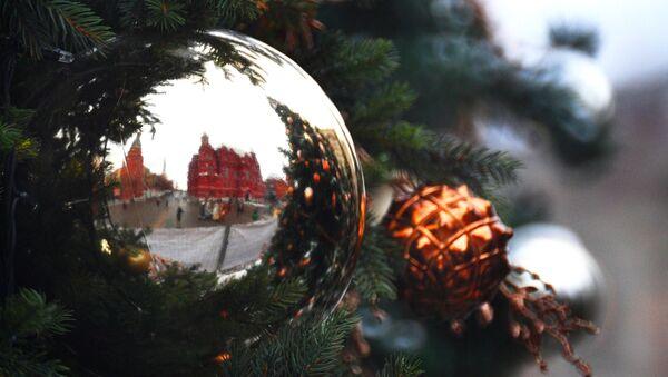 Los muros de la Plaza Roja de Moscú reflejados en un adorno navideño - Sputnik Mundo