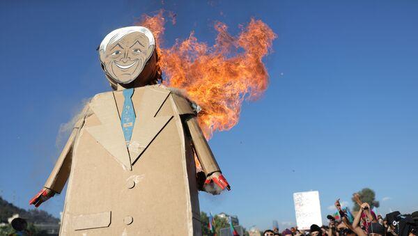 Figura de cartón del presidente chileno, Sebastián Piñera, incendiada por manifestantes - Sputnik Mundo