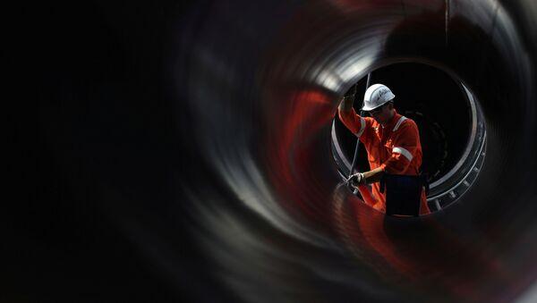 Un trabajador es visto a través de una tubería en el sitio de construcción del gasoducto Nord Stream 2 en Rusia - Sputnik Mundo