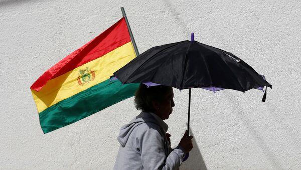 Una mujer con un paraguas y una bandera de Bolivia - Sputnik Mundo