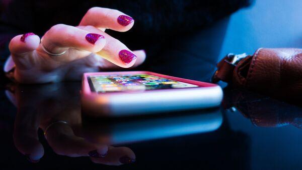 Una mujer utiliza su teléfono móvil - Sputnik Mundo