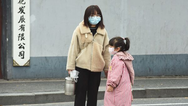 Una mujer y una niña usando máscaras para no contagiarse en China - Sputnik Mundo