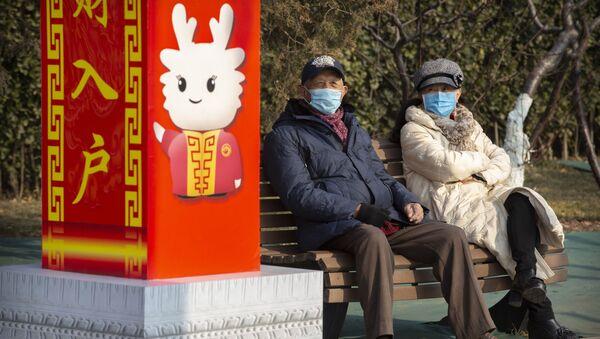 Personas con mascarillas en un parque de Pekín, China - Sputnik Mundo