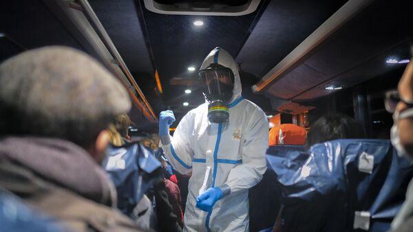 Офицер в защитной одежде инструктирует эвакуированных из Ухани, Китай - Sputnik Mundo