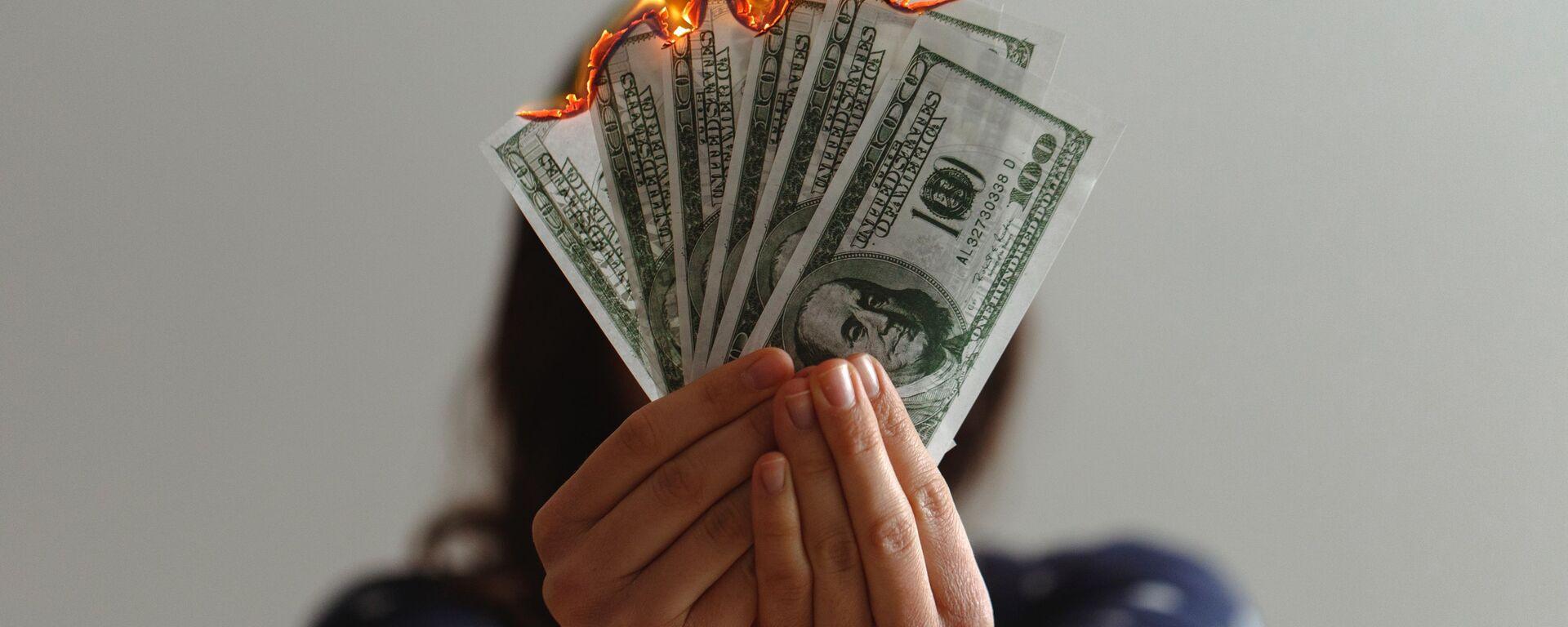 Dólares estadounidenses en llamas (imagen referencial) - Sputnik Mundo, 1920, 15.09.2021