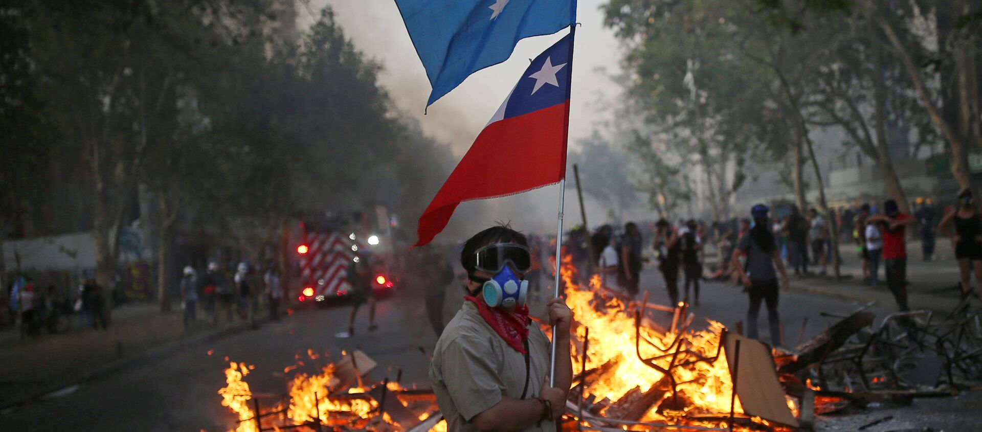 Manifestante con bandera de Chile y bandera mapuche en una barricada - Sputnik Mundo, 1920, 08.02.2020