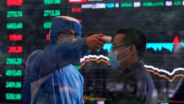 Revisión de una persona para detectar si tiene coronavirus cerca de la Bolsa en Shanghái, China - Sputnik Mundo