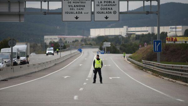 Un oficial de Policía en la carretera cerrada cerca de Igualada, España - Sputnik Mundo
