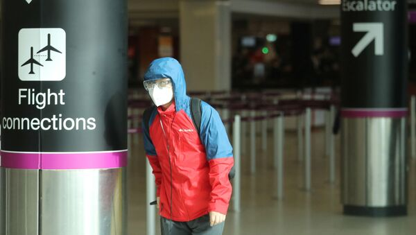 Un pasajero con una mascarilla debido al coronavirus - Sputnik Mundo