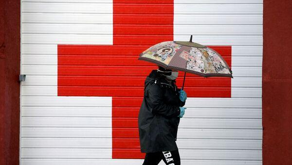 Una persona cerca de la oficina de la Cruz Roja en Oviedo, España - Sputnik Mundo