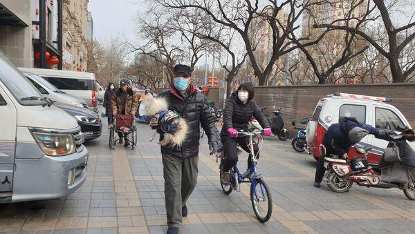 Unos chinos con un perro (imagen referencial) - Sputnik Mundo