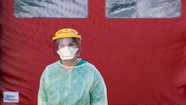 Una médica con mascarilla - Sputnik Mundo