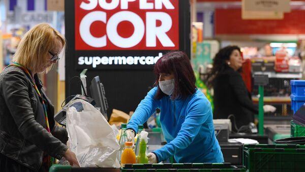 Cajera atendiendo a una clienta en un supermercado de Madrid - Sputnik Mundo