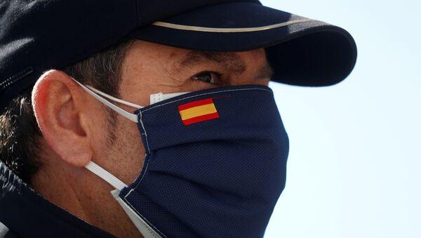 Una persona con una mascarilla que lleva la bandera esañola - Sputnik Mundo