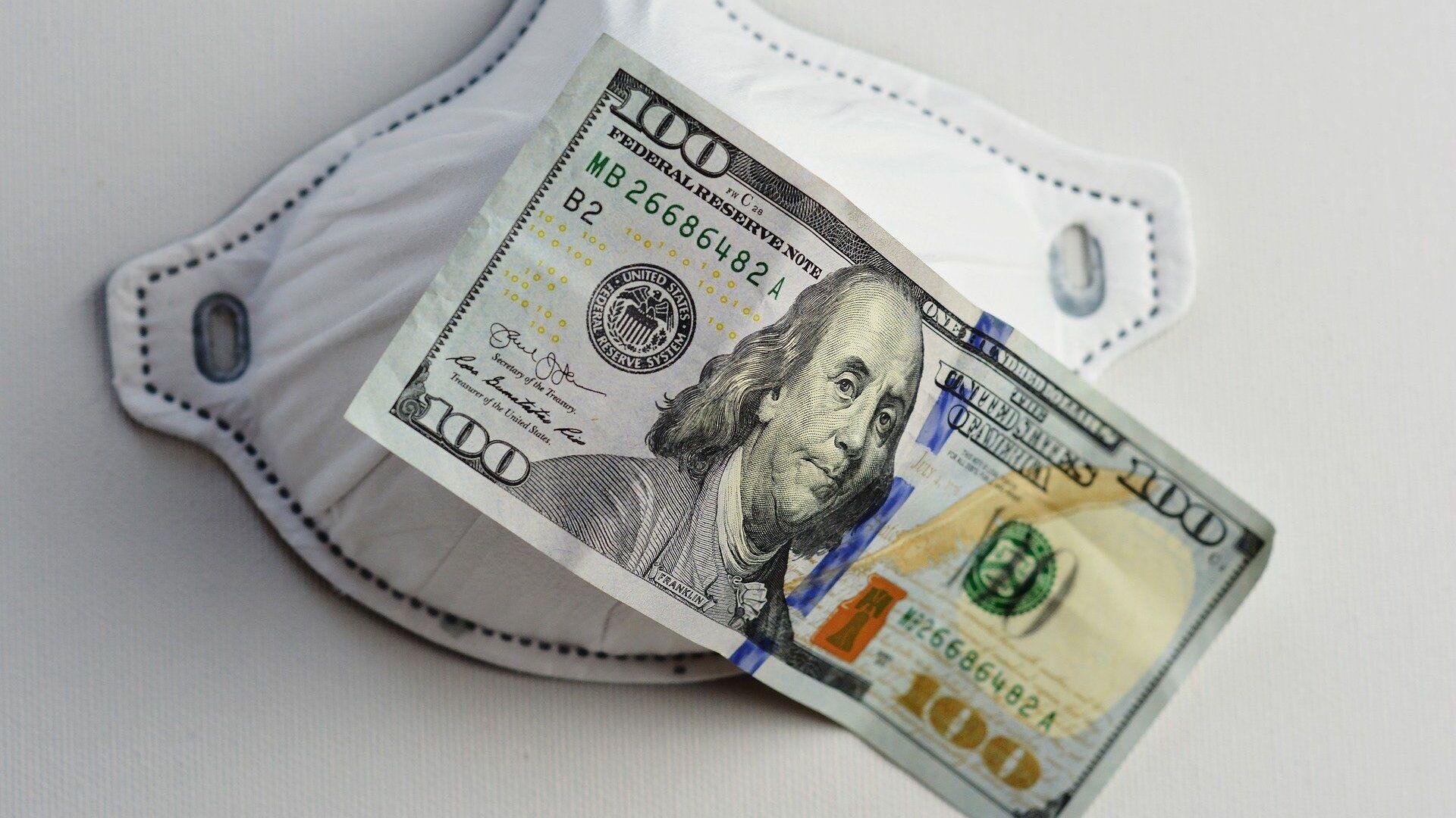 Una mascarilla junto a un billete de 100 dólares. Imagen referencial - Sputnik Mundo, 1920, 01.10.2021