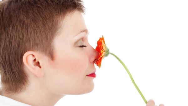 Una mujer huele una una flor - Sputnik Mundo
