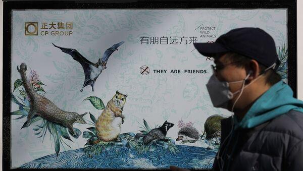 Un hombre con mascarilla puesta pasa cerca de un póster publicitario que promueve la protección de los animales salvajes - Sputnik Mundo