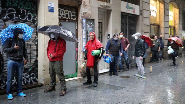 La gente con mascarillas durangte el brote de coronavirus en España - Sputnik Mundo