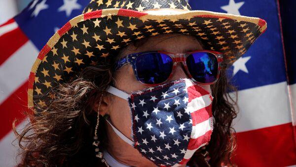 Una persona con una mascarilla con la bandera de Estados Unidos - Sputnik Mundo