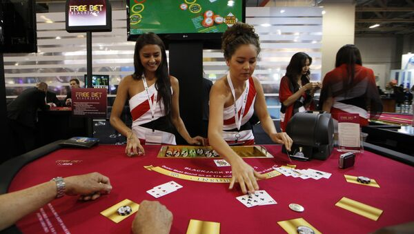 Attendants conduct play with the visitors over a Black Jack gaming table during the Global Gaming Expo Asia in Macau - Sputnik Mundo