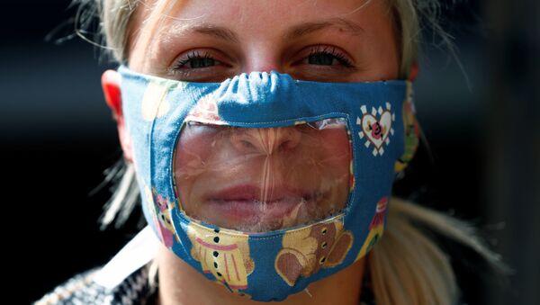Una mujer con mascarilla transparente - Sputnik Mundo