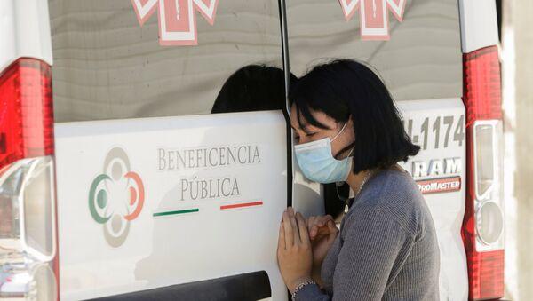 Mujer con mascarilla junta a ambulancia - Sputnik Mundo