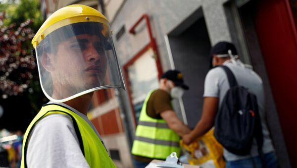 Un voluntario durante el brote de coronavirus en España - Sputnik Mundo