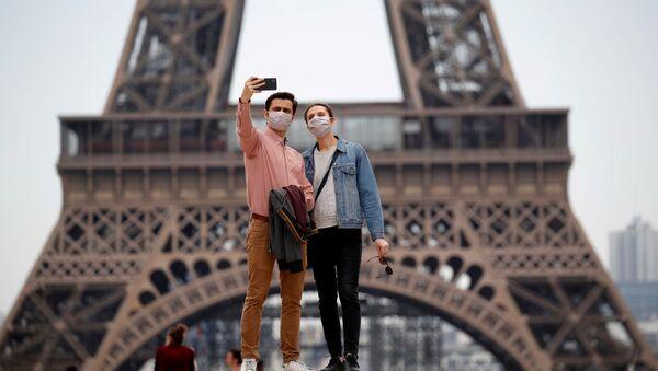 Una pareja con mascarillas cerca de la Torre Eiffel - Sputnik Mundo