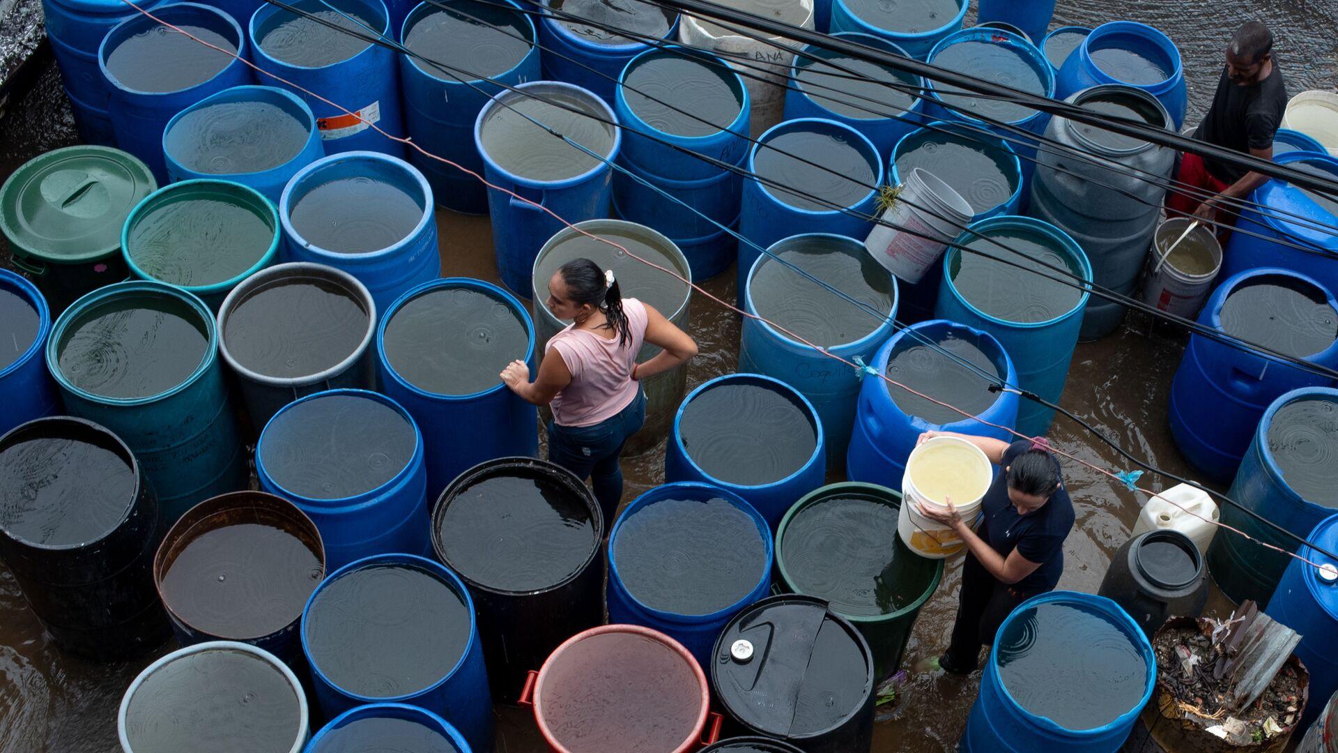 La gente llena los envases plásticos con agua en Petare, Caracas - Sputnik Mundo, 1920, 02.09.2021