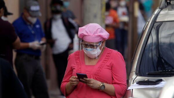 Una mujer con mascarilla en Honduras - Sputnik Mundo