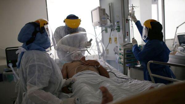 Los médicos atienden a un paciente con coronavirus en Bogotá - Sputnik Mundo