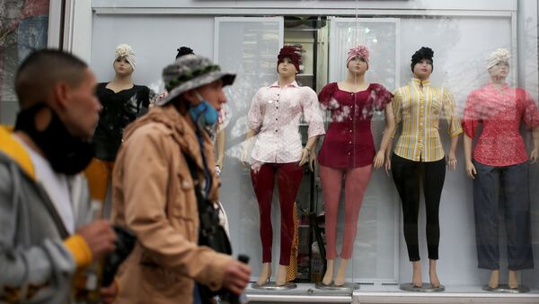 Colombianos caminan frente a tienda de ropa en Bogotá - Sputnik Mundo
