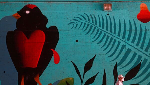 Un hombre en mascarilla pasa al lado de un muro con graffiti en Madrid - Sputnik Mundo