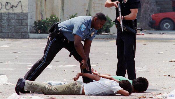 Un agente de Policía detiene a dos sospechosos de saqueo durante los disturbios de Los Ángeles - Sputnik Mundo
