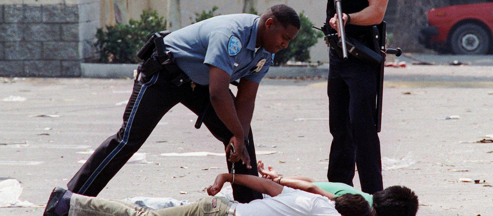 Un agente de Policía detiene a dos sospechosos de saqueo durante los disturbios de Los Ángeles - Sputnik Mundo, 1920, 05.07.2020