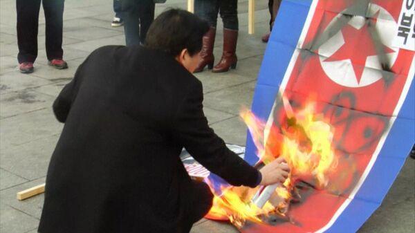 Activistas queman bandera de Corea del Norte en Seúl en protesta por la prueba nuclear - Sputnik Mundo